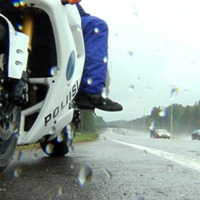Moottoripyöräpoliisi sadesäässä tienpientareella