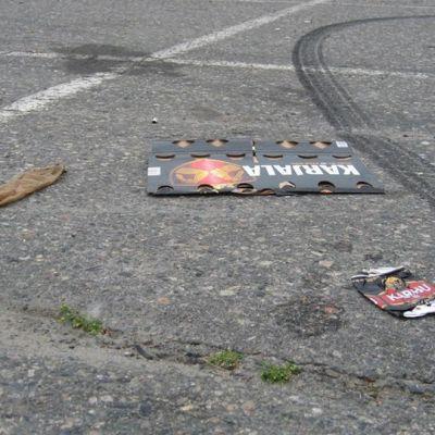 Sukkahousut, olutpakkauksen kuori ja tyhjä olutpurkki litissä asfaltilla. Mustaa raitaa auton kumista.