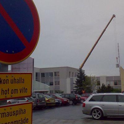Kuvassa kirjapainoyhtiön entinen kiinteistö Prisman nurkalta nähtynä. Nosturi nostaa rakennuksesta tavaraa.
