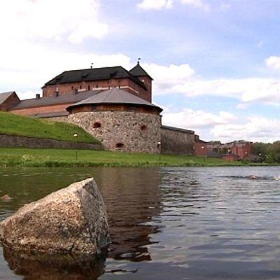 Ihminen ui Hämeen keskiaikaisen linnan rannassa