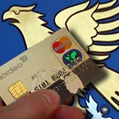 Käsi pitelee luottokorttia Kotkan vaakunan edessä.