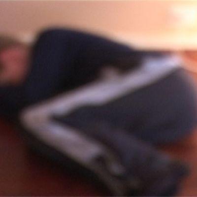 Tunnistamaton nuori makaa lattialla polvet koukussa