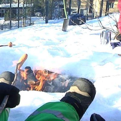 Lapsi grillaa makkaraa nuotiolla.