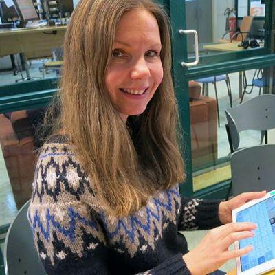 Hanna Kaisti näppäilee tablettitietokonetta