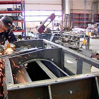 Työntekijä rälläköi metalliosia JPT-Industia Oy:ssä.