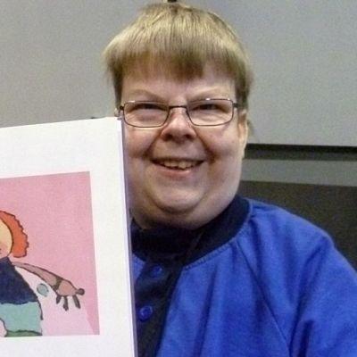 Kimmo Tolvanen näyttää kirjan sivulta maalaustaan