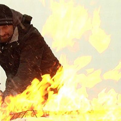 Mies sammuttaa liekkejä palosammuttimella