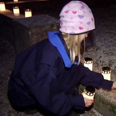 A girl sets a candle by a grave.