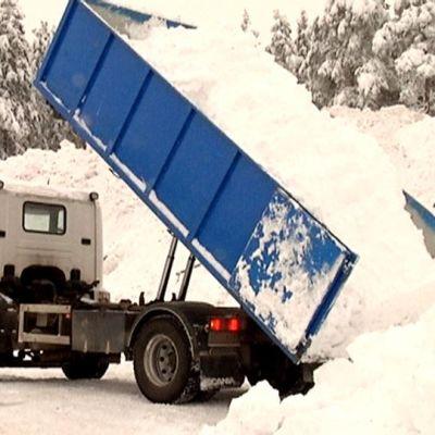 Kuorma-auto kippaa lunta lumenkaatopaikalle.