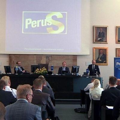 Perussuomalaisten kesäkokous ja edustajat istuvat Kotkan valtuustosalissa.