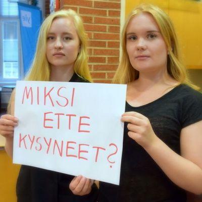 """Veera Kärki (oik.) ja Aino Ruotsalainen pitävät lappua, jossa lukee """"Miksi ette kysyneet?"""""""