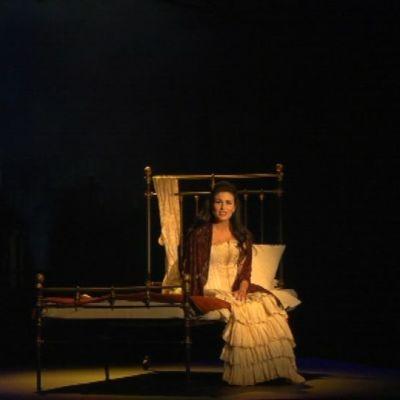 Nainen laulaa sängyllä istuen.