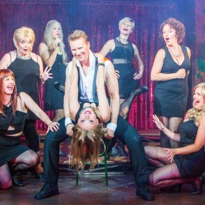 naiset piirittävät miestä teatterin lavalla