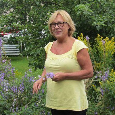 Nainen omassa puutarhassaan.