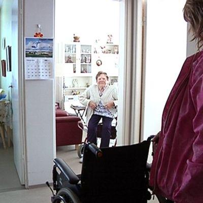 Kuvassa Elvi Vero istuu rollaattorin penkillä asunnossaan. SPR:n ystävä odottaa ovella.