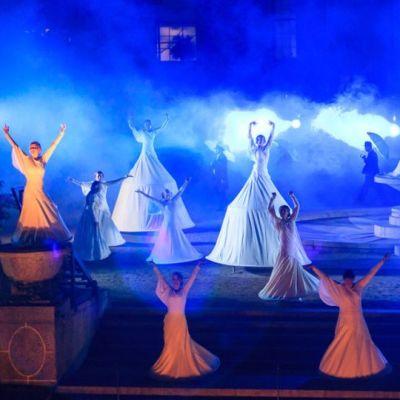 Tanssijoita sinisessa valossa suihkulähteen ympärillä