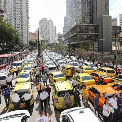 Kymmeniä taksiautoja tukkii tien.