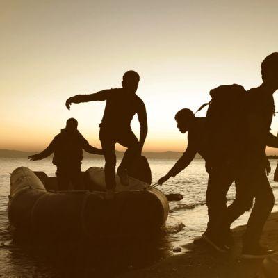 Henkilöitä nousemassa rannalle kumiveneestä.