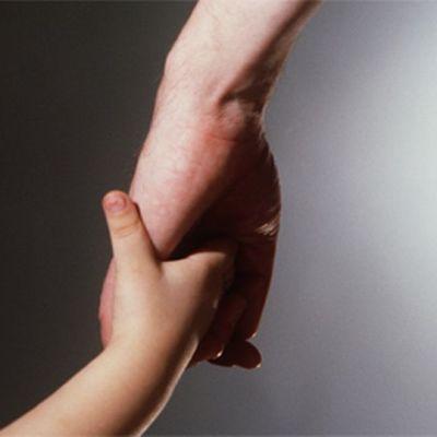 AIkuinen ja lapsi käsi kädessä