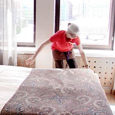 Hotellisiivooja petaa sänkyä hotellihuoneessa.