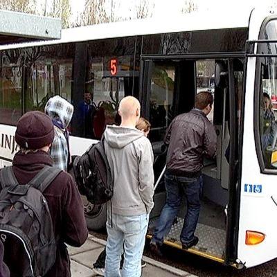 Matkustajat nousevat linja-autoon skinnarilassa.
