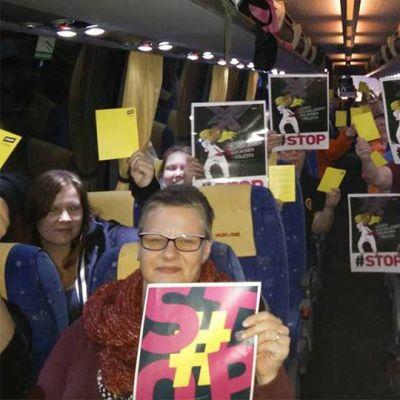 Pietarsaarelaisia ja kokkolalaisia matkalla Helsinkiin, ihmisillä käsissään mielenilmauksen julisteita #STOP