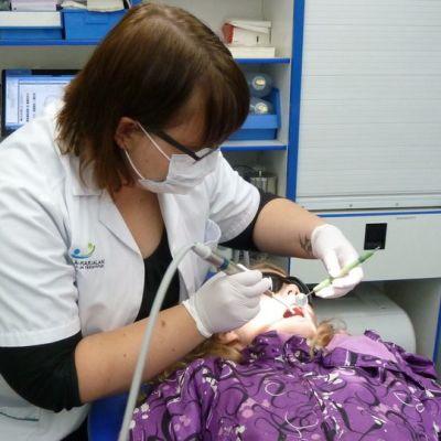 Suuhygienisti Terhi Luukkonen tarkastaa 5.-luokkalaisen tytön hampaita Mallu-autossa.