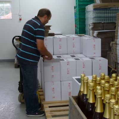 Mies seisoo pakkaamossa pullolaatikoiden äärellä.