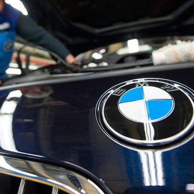 Mies huoltamassa BMW:n moottoria.