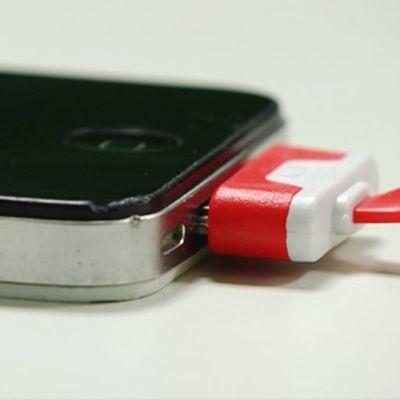 Lähikuva laturinjohdosta ja Iphone-puhelimesta.