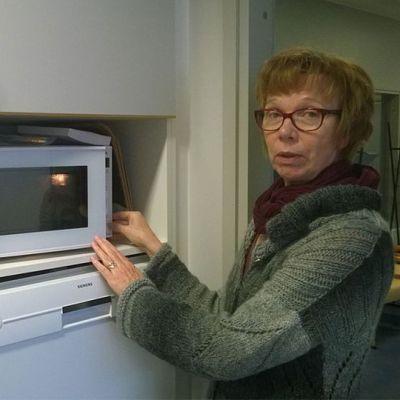 Kuvassa Pirkko Kivistö kertoo kuinka mikroaaltouunin käyttöön perehdytetään.