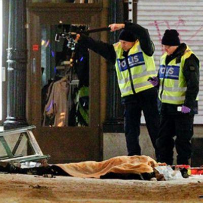 Poliisi tutkii mahdollisen iskun tekijäksi epäillyn ruumista.