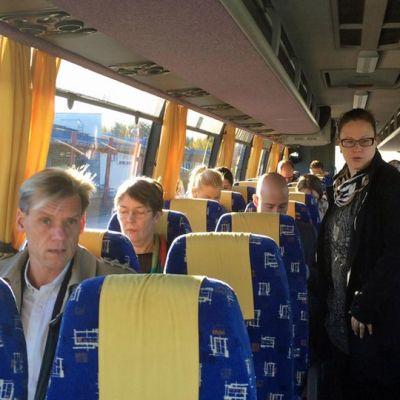 Ihmisiä, muun muassa Satu Hassi, linja-autossa.