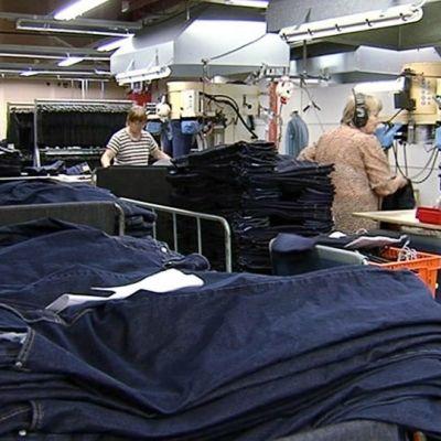 Farkkuja ja työntekijöitä farkkutehtaalla.