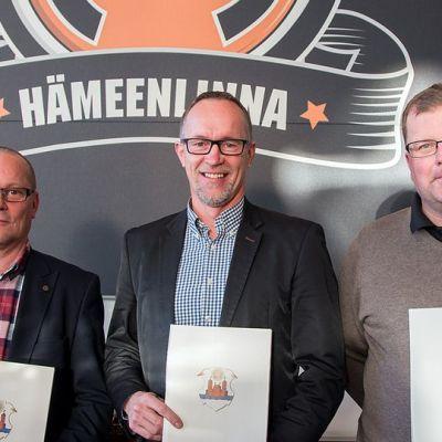 Kolme miestä polleena kuvassa kunniakirjat käsissään
