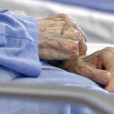 lähikuva pyjamaan pukeutuneen vanhuksen käsistä
