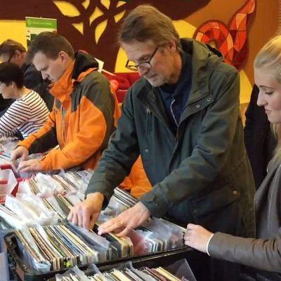 Kuusu ihmistä seisoo pöydällä olevien äänilevylaatikoiden edessä ja etsii niistä itselleen sopivia levyjä.