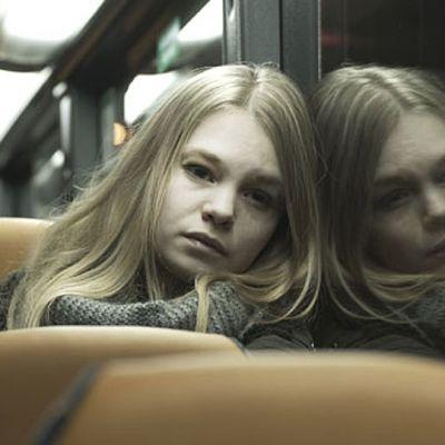 Tyttö istuu bussissa ja hänen kuvansa heijastuu ikkunasta.