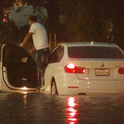 Mies nousemassa tulvavedessä olevasta autosta.