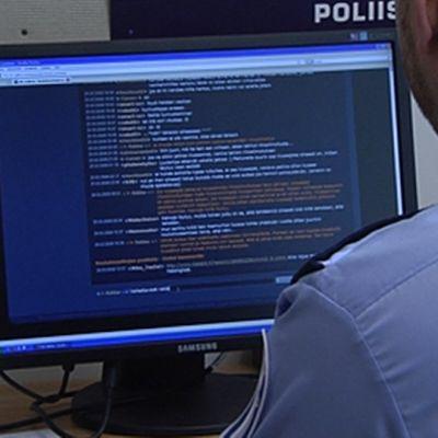 Poliisi istuu tietokoneen näytön äärellä virka-asussaan.