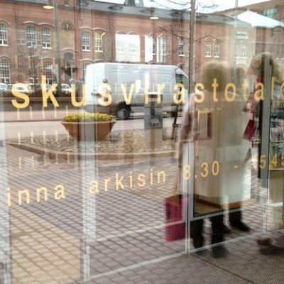 Keskusvirastotalon ovesta heijastuu ihmisiä
