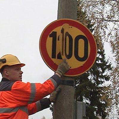 Työmies vaihtamassa talvinopeusrajoitusta liikennemerkkiin.