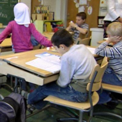 Ala-asteen koululuokassa on myös maahanmuuttajien lapsia. Kuvan etualalla maapallo, joka on pyöritetty Indonesian kohdalle.