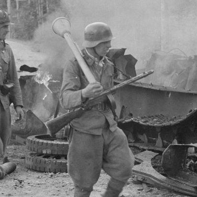 Jalkaväkirykmentti 12:n miehet ohittavat saksalaisen rynnäkkötykin tuhoaman T34-tankin 30. kesäkuuta 1944. Vasemmalla panssarijääkäri Eino Heikkilä, edessä panssarinyrkitolallaan kersantit Kalle Niemelä ja Heino Nikulassi. Nikulassi kaatui kuvaamista seuraavana päivänä.