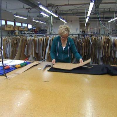 Työntekijä leikkaa kangasta miesten pukuun Salmutexin pukutehtaalla.