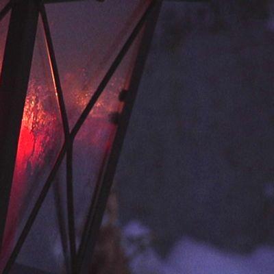 Punainen kynttilä lyhdyssä hautausmaalla.