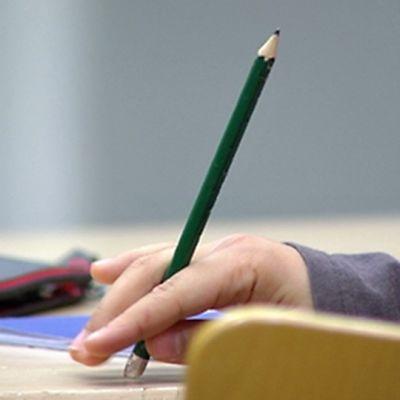 Oppilas pyörittelee vihreää, pitkää kynää kädessään.