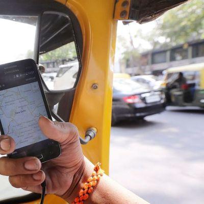 Intialainen tutkii uber-sovellusta autossaan Delhissä.