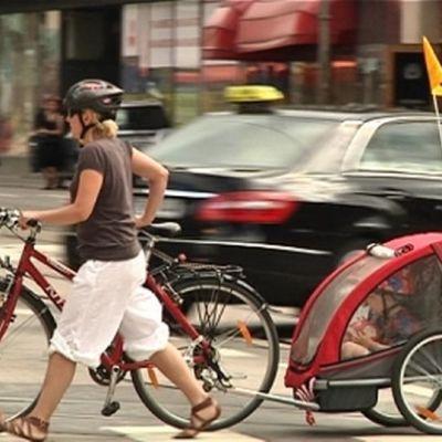 Nainen taluttaa pyörää Hämeentien yli.