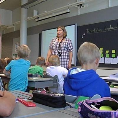 Oppilaita ja opettaja luokassa.